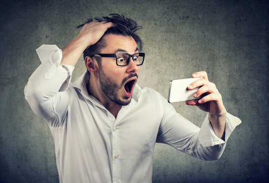 Shocked man watching phone and pulling out hair