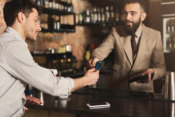 Bartender accepting credit card at bar counter