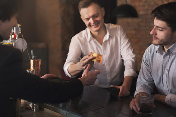 Man giving credit card to bartender in pub