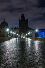 Karlsbrücke in Prag über die Moldau am Morgen. Nasses Kopfsteinpflaster.