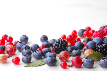 Various fresh berries close-up including blueberries, raspberries, blackberries currants and gooseberries on a white wooden background.