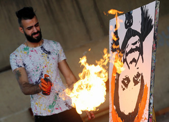 Egyptian speed painter Albert Magdy uses fire on an inverted painting of Egyptian actor Adel Imam in Cairo