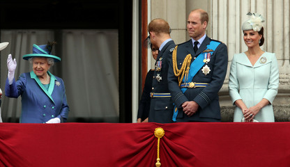 Britain's Queen Elizabeth, Meghan, Duchess of Sussex, Prince Harry, Prince William, Catherine, Duchess of Cambridge stand on the balcony of Buckingham Palace as they watch a fly past to mark the centenary of the Royal Air Force in central London