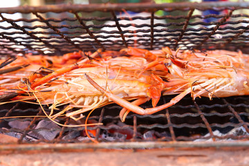 Close up of shrimp grilled on a hot charcoal stove in the party at camping.