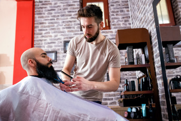 Hairdresser cutting a client's beard with scissors