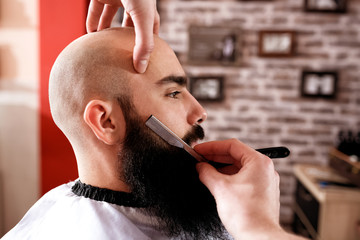 Master makes beards correction in barbershop salon