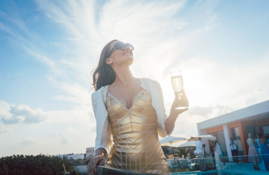 Woman having champagne at summer party