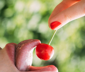 Sexy berry and tongue. Young female is tasting red cherry. Sensual woman, erotic. Creative concept of healthy lifestyle. Open mouth, cherry on tounge and nature background. Red Nail Polish Manicure