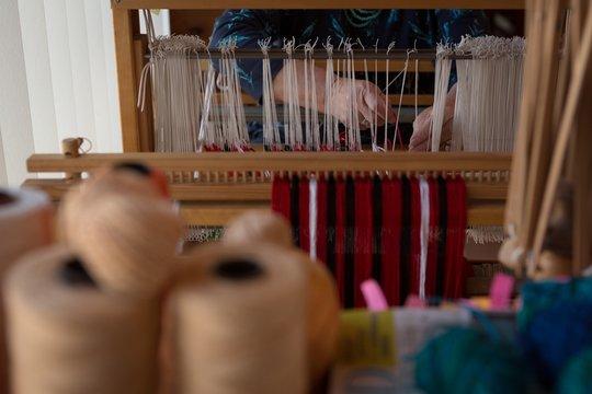 Senior woman weaving silk at shop