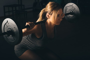 fitness, sport, powerlifting and people concept - sporty woman exercising with barbell in gym