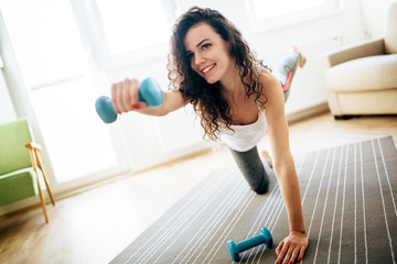 Young attractive sportswoman doing exercises at home