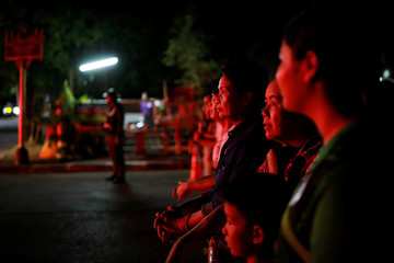 Onlookers watch the last ambulance carrying people rescued from Tham Luang cave complex in Chiang Rai