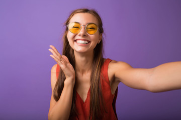 Portrait of a cheerful woman making selfie photo over purple background.Studio portrait of beautiful woman smiling with white teeth and making selfie, photographing herself over violet background