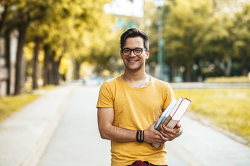 Young male student standing at the college yard.He holding a book and looking at camera.