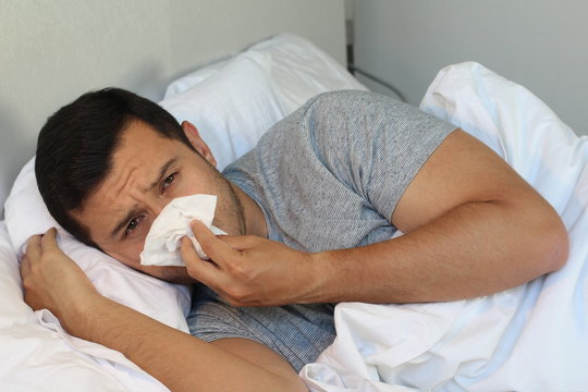 Man blowing his nose in bed