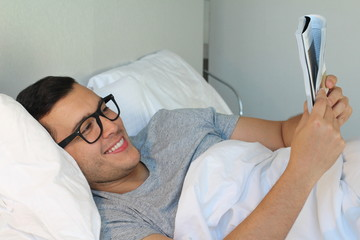 Man reading a magazine in bed