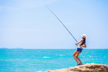 woman standing fishing on the rock at the sea