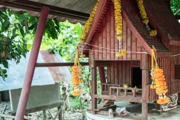 spirit house in thailand with garland and some wreathes,