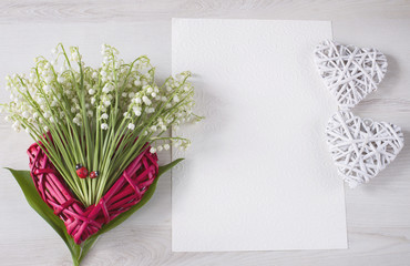 on a light background a red heart made of straw and a bouquet of lilies of the valley and a writing paper, and two hearts