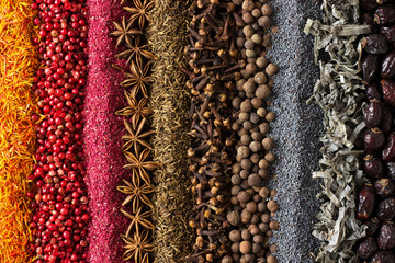Fototapete - Various spices and herbs are scattered on table. Seasoning background for packaging with food.