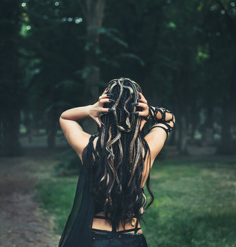 Image of Gorgon Medusa, braid hair and golden snakes, close-up portrait from the back without a face. A woman shows hands with long, black nails. Mystical photosession in the forest