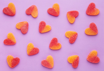 Heart shaped candy pattern on a purple background. Jelly candies viewed from above. Top view. Repetition concept