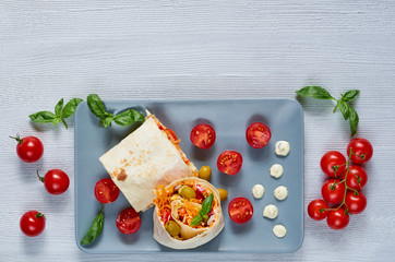 Traditional arabic food with copy space. Shawarma sandwich or lavash snack with fresh vegetables and sauce on the gray plate decotated with cherry tomatoes, basil leaves. Eastern cuisine. Top view
