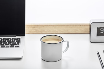 desktop with vintage mug; laptop; clock, pen and plant