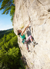 The woman climbs the rock.