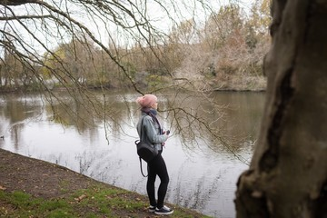 Young woman with back pack standing near river coast