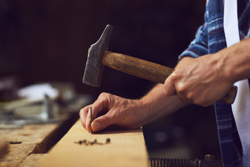 Carpenter hammering a nail into wooden plank in a carpentry shop