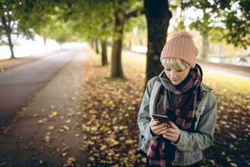 Young woman in warm clothing using her mobile phone