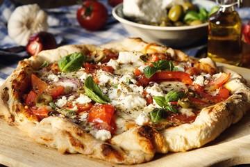 Herzhafte hausgemachte Pizza mit Feta Käse, Tomaten, Oliven und Basilikum