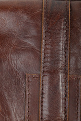 Stitched brown leather parts. Details of a man's bag
