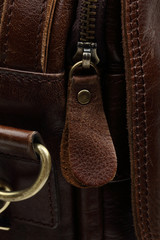 Zip fastener on a brown leather surface close-up