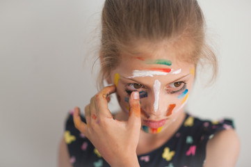 cute little girl with face painted with various colors touching eyelash