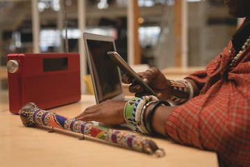 Maasai man in traditional clothing using mobile phone