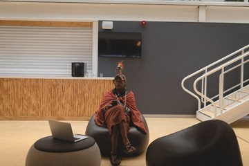Maasai man in traditional clothing relaxing on seat