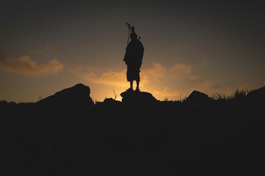 Silhouette of maasai man standing on rock