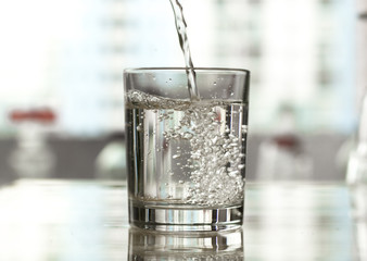 Purified and fresh drinking water is poured from the bottle into a glass beaker.
