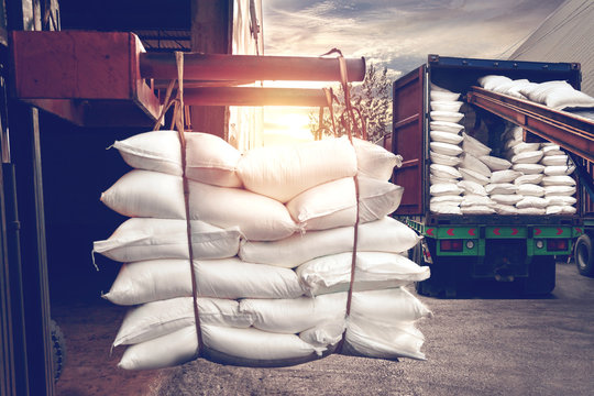 Forklift handling white sugar bag from warehouse for stuffing into container for export, vintage tone.