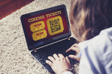 Woman using a laptop to buy cinema tickets online in a website.