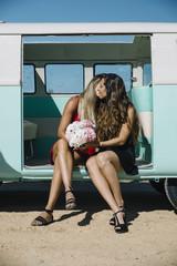 Two lesbian women kissing in the old van