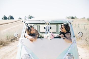 Two happy lesbian women in the old van
