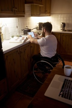 Disabled man using digital tablet in kitchen