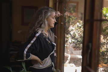 Thoughtful mature woman looking through window