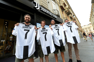 Juventus supporters hold, after buying, the original Juventus' jersey printed with the name and number of Cristiano Ronaldo after his transfer to Juventus in Turin