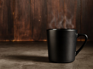 coffee in a black mug with dark wood background
