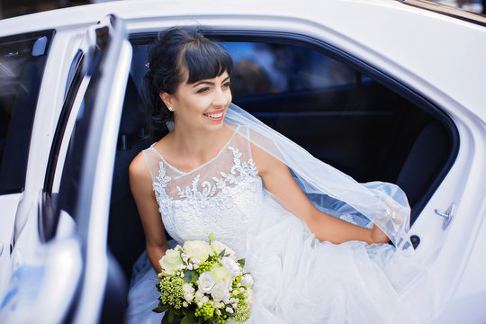 Joyful bride in white wedding dress and veil holds bouquet of roses, sitting in white luxury car