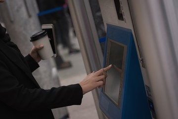 Woman using ticket machine at railway station